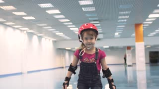 Child on roller skates. Girl learns to skate in helmet