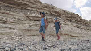 children are travelers on a hike. A small tourist with backpacks are walking along the mountainous terrain.