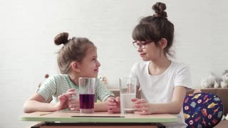 children conduct chemical experiments at home. two little girls observe a chemical reaction. Science for children