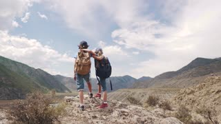 children of the travelers embrace and enjoy the beautiful view of the mountains. two little girls with backpacks on a hike