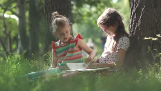 Children read a book outdoors sitting on the grass near a tree. Two little girls have fun together