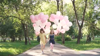 children run through the Park with a huge bunch of colorful balloons. two little girls with balloons on a background of green trees. slow motion