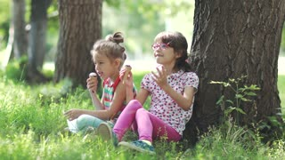 children sit on the grass in the summer Park and talk. two little girls eating ice cream and enjoying a summer day