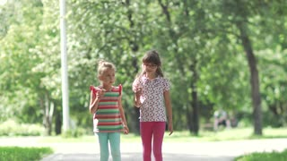 Children walk around the summer park and eat ice cream. Little girl smeared her face with ice cream