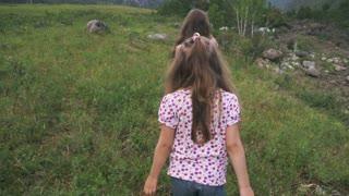 children walk down the meadow. two little girls traveler was walking across a field near a mountain river