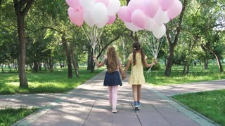 children walk through summer Park with balloons. two little girls are holding a lot of colorful balloons. the view from the back