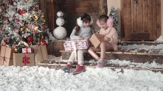 Christmas or New Year. children are looking at presents in beautiful Christmas boxes. two little girls on a christmas tree background