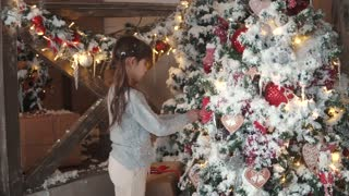 Christmas or New Year. children enchantingly look at the New Year tree. little girl in fur ears hang Christmas toys on the Christmas tree