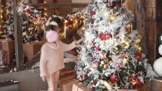 Christmas or New Year. children enchantingly look at the New Year tree. little girls in fur ears hang Christmas toys on the Christmas tree