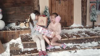 Christmas or New Year. children exchange gifts for Christmas. two little girls on the background of the New Year's decoration