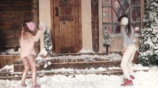 Christmas or New Year. children have fun playing in artificial snow. Christmas decoration. Two little girls on the porch of the house. slow motion