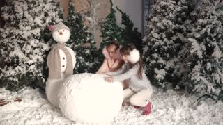 Christmas or new year. children make a snowman. two little girls make a ball of snow