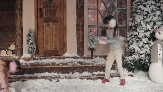 Christmas or New Year. children playing snowballs on the porch of the house. two little sisters are having fun and playing on New Year's holidays. slow motion