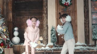 Christmas or New Year. happy children throw up snow. the children enjoy the Christmas holidays. Two little girls on the porch of the house. slow motion