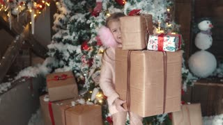 Christmas or new year. little girl holding in hands a box with gifts and smiles slyly. the child received many presents on Christmas