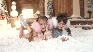 Christmas or New Year. portrait of two little sisters in fur headphones. children lie on artificial snow