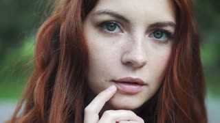 Close-up portrait of a beautiful red-haired girl with expressive eyes. 20s