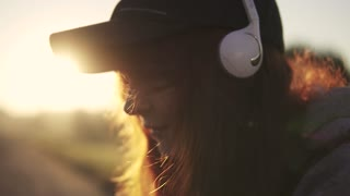 close-up portrait of a red-haired girl in headphones. Girl listening to music on headphones at sunset