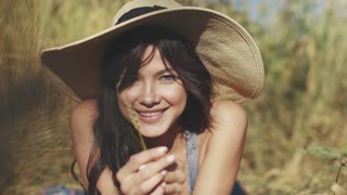 close-up portrait of a village girl in a straw hat with a straw in her hands. A cute girl smiles and looks at the camera