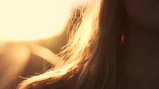 closeup portrait of a beautiful girl at dawn. a young woman touches hair. the sun's rays and glare