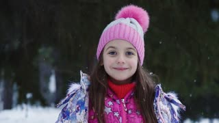 closeup portrait of a little girl under the snow. child on winter walk. slow motion