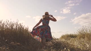 concept of carefree summer and joy. A young woman runs into a field with tall grass. A girl in a rustic dress and a straw hat. Back view. slow motion