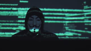 concept of computer security and security in the network. robber in the mask at the computer. the hacker breaks the computer code. binary codes projections and animation in background