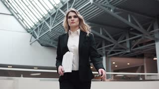 confident business woman is walking along the production building. the manager is in a hurry to meet with clients or a business partner. woman in business suit holding documents in hands