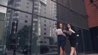 confident business woman walking in the background of a modern business center. girl holding blueprints and talking on the go. women in business clothes on the street. Slow Motion
