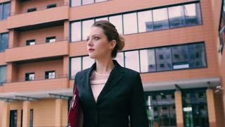 Confident business woman walking through the business district. Beautiful young girl in a jacket holds a red folder for papers in hands. SLOW MOTION