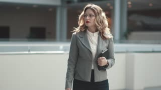 confident business woman walking through the lobby of a modern office building
