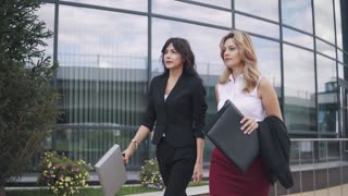 confident business women walking down the street. business partners are talking on the go
