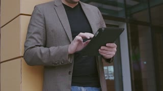 Confident businessman working on a tablet computer. Man in a jacket and glasses on the background of a modern business building. Smart watch and tablet computer in hands.