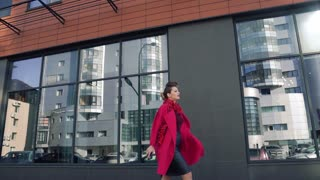 confident woman with a beautiful unusual hairdress walks through the spring city. Girl on the background of modern architecture. SLOW MOTION