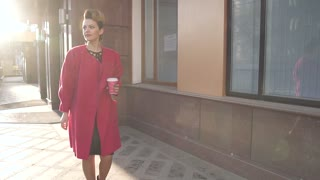 confident woman with a beautiful unusual hairdress walks through the spring city. Girl on the background of modern architecture with coffee. SLOW MOTION