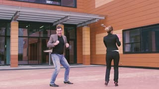 crazy dancing businessmen. business man and business woman celebrating success and dance. handsome man and beautiful woman on the background of the business building. SLOW MOTION