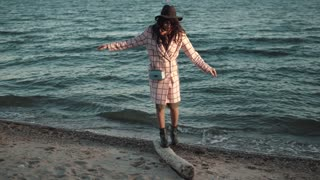 cute girl in autumn coat walks along the beach at sunset. young woman enjoying warm autumn day on the water. the girl goes funny on a log trying to keep the balance