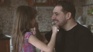 Dad and daughter brush their teeth together. Father and little girl laugh and have fun together.