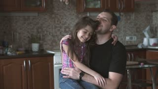 Dad and little daughter hold each other tightly. Little girl kisses her father on the cheek. slow motion