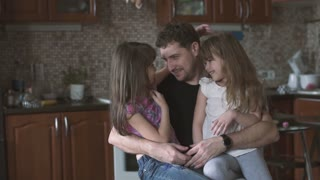 dad kisses and hugs his little daughters sitting on his lap. father and children. slow motion