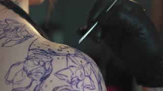 drawing a tattoo on the shoulder close up. master tattoo makes a rotary tattoo machine gun