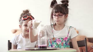 entertaining science. children conduct a scientific experiment at home