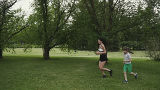 family Jogging in the woods. young sport mother and daughter doing sports outdoors