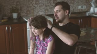 father plaits pigtails to a small daughter. little girl and her father spend time together and have fun