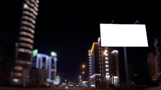 footage of Time lapse urban scene with an illuminated empty billboard on the side of a street with cars in motion