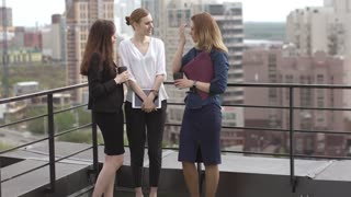 Friends drink coffee standing on the roof. Business woman during lunch break. slow motion