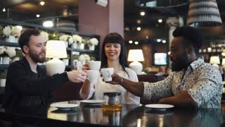 friends drink tea and have fun. a company of three friends in a restaurant and a cafe. two young men and a girl are sitting at a table in a cozy restaurant.