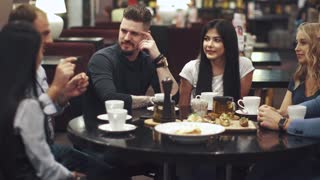 friends laugh and have fun sitting at a table in a restaurant. A company of friends spends time together and enjoys socializing.
