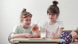 funny children conduct a chemical experiment and mix reagents. kids are surprised and happy watching the chemical reaction