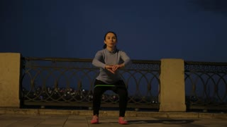 girl does sports exercises with a rubber band on the embankment. sportsman trains on the night city's lone city alone